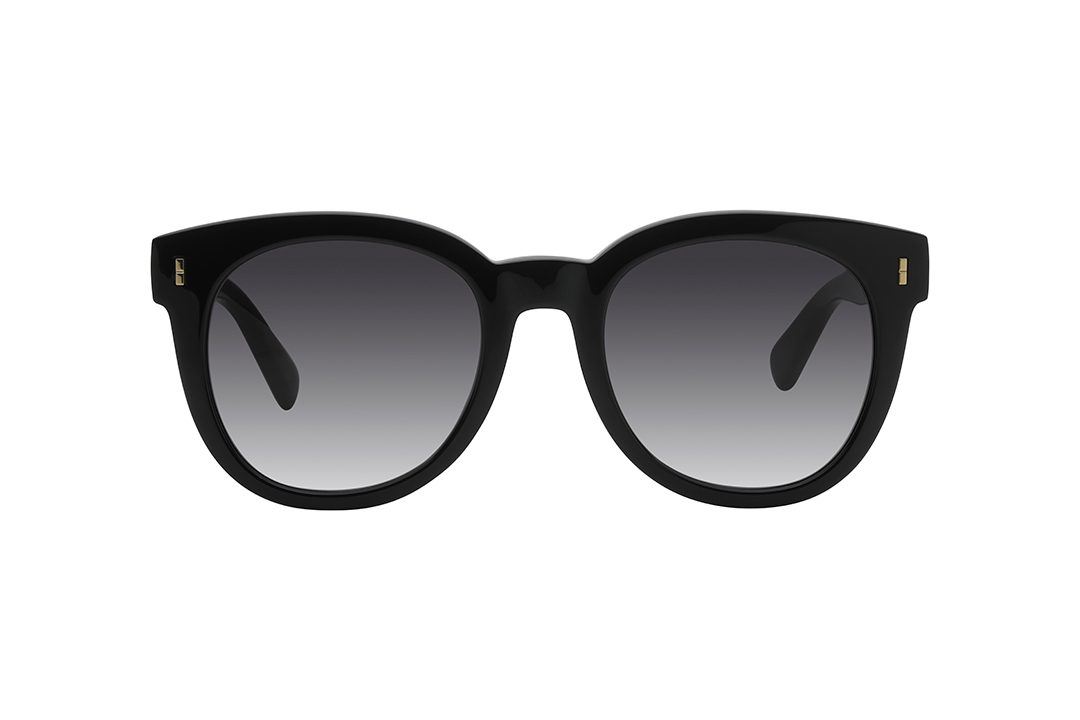 משקפי שמש עגולות עם פינות עליונות במראה חתולי, חזית בצבע שחור עם עיטור מלבני מינימליסטי בצבע זהב בפינות, זרועות בצבע זהב מרוקעות בשתי נקודות עדינות בכלות סיומת בצבע שחור. עדשות בצבע אפור