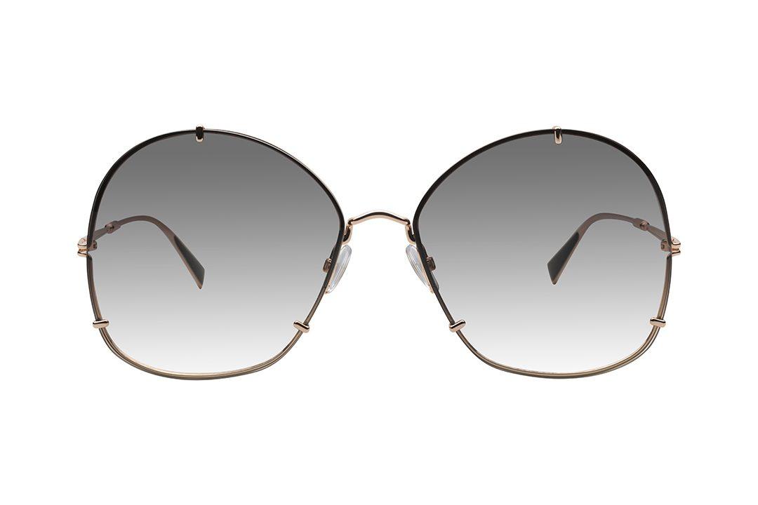 """משקפי אובר סייז בעלי צורה ייחודית:. עדשות בצורה שחלקה העליון מעוגל וחלקה התחתון ריבועי, מסגרת פנימית דקיקה בצבע זהב, המשלבת 3 """"זרועות"""" שיוצרות מראה של קליפון, זרועות דקיקות בצבע זה ועדשות בגוון אפור-חום"""